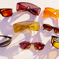 Photo of several pairs of glasses in the sunshine with the sun reflections cast in the sunshine