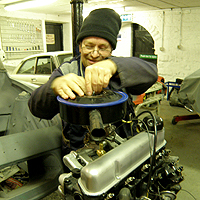 Photograph of John working on a car
