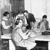 Old black and white photo of children at school making baskets
