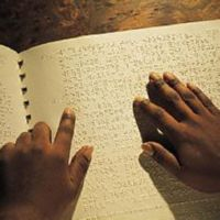 Photograph of braille being read by 2 hands