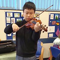 Photo of Zheyuan at SRSB playing violin