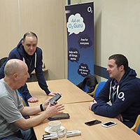 Photograph of previous Guru Day at SRSB showing people chatting about a device