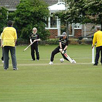 Photograph of people playing cricket outdoors