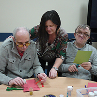 Photograph of clients and staff working on a craft activity in the group