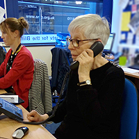 Photograph of a volunteer speaking on the phone in the office