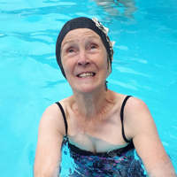 Photo of someone in a swimming pool smiling and wearing a swimming hat