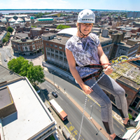 Photograph looking down at someone abseiling down a building with a view of the city in the background