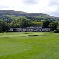 Photograph of Sickleholme golf course with clubhouse and hills in background