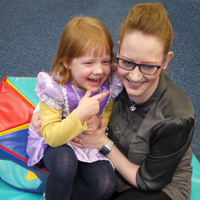 Photograph of one of SRSBs young clients with her mum