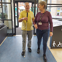 Photo of a volunteer guiding someone with sight loss